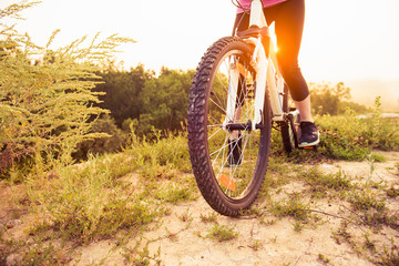 Girl on mountain bike rides on the trail on a beautiful sunrise. Bicycle wheel closeup