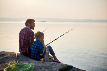 Back view portrait of adult man and teenage boy sitting together on rocks fishing with rods in calm waters of blue lake at dusk, both wearing checkered shirts