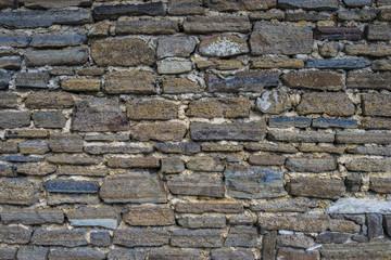 Ancient old dark regular stone wall