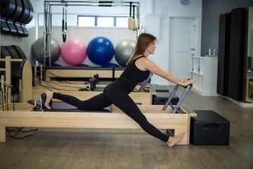 Zdecydowana kobieta ćwiczy ćwiczenia rozciągające na reformatorze