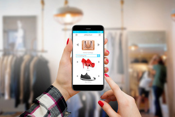 Women holding moder phone with shopping interface in hands inside clothing store and shopping online