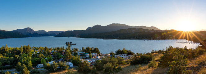 Panoramic view of the lake Lac de Serre Poncon in the French Alps and a campsite with sunset