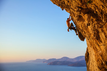 Young man struggling to climb challenging route on cliff at sunset