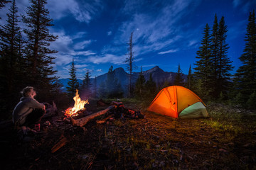 Man looking up at the stars next to campfire and tent at night