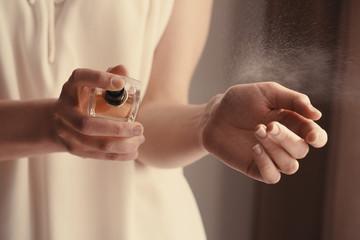 Piękna młoda kobieta z butelką pachnidło w domu, zbliżenie