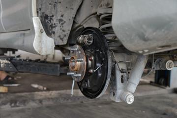 Car brake repairing on scissor cranes lift in garage