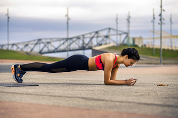 Young and attractive woman in sportswear is making the plank in urban park, Barcelona, Spain. Minimalism concept.
