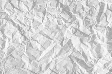 Surface of crumpled paper highlighted by light. Stressed, illuminated sheet of paper paper.