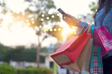 Kobieta używa smartphone z torba na zakupy w rękach