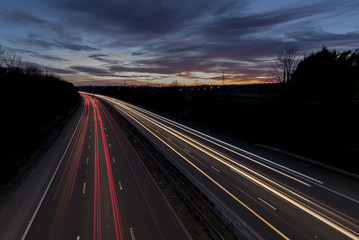 A UK motorway, at sunset, with light trails created by the traffic on the road