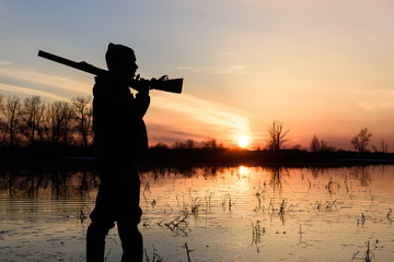 Silhouette of a hunter at sunset in the water with a gun.