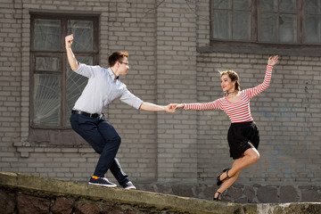 young couple dancing swing outside in front of old brick house