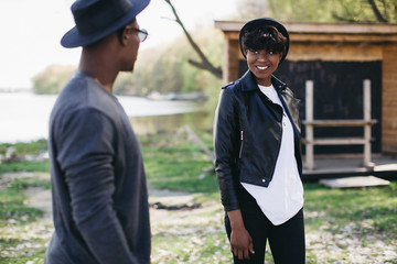 A beautiful and stylish young african couple in sunglasses and hats walking on a outdoor of summer.