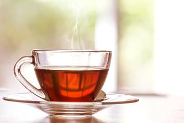 Zamyka w górę ciepłej czarnej herbacianej filiżanki na drewnianym stole w żywym pokoju, relaksuje z herbacianego czasu pojęciem