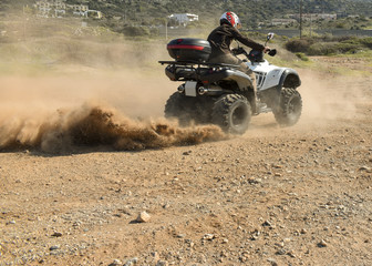 A man riding ATV in sand in a  helmet.