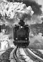 Historic locomotive leaving the station. Retro train on the rails. Sky full of smoke. Image in black and white.