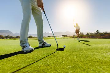 Golfista kładzenie piłki z żeńskim partnerem trzyma flaga na golfa cou