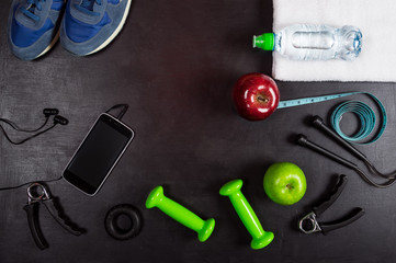 Fitness equipment background. Dumbbell, skipping rope, apple, water bottle, massage ball, towel, smartphone and headphones, sneakers on black background. Top view