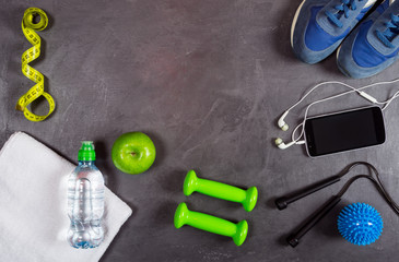 Fitness equipment background. Dumbbell, apple, water bottle, towel, smartphone and headphones, measuring tape, sneakers on grey background. Top view