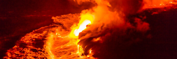 Lava flow falling in ocean waves in Hawaii from Hawaiian Kilauea volcano at night. Molten lava washed by the sea water crashing in, Big Island, USA.