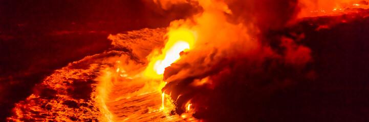 Przepływ lawy spadający w fale oceanu na Hawajach z wulkanu Hawajski Kilauea w nocy. Stopiona lawa obmywana przez wodę morską, Big Island, USA.