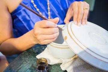 Tajlandzka kobieta używa muśnięcie malującego projekt na zbiornikach, ceramiczna tradyci sztuka Tajlandia