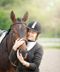 Attractive Young Woman Embracing her Horse