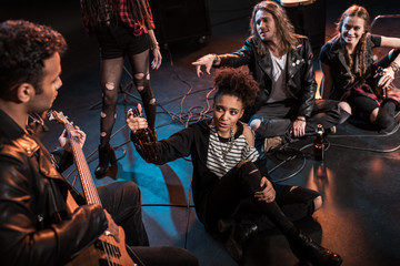 Young rock and roll band drinking beer after concert on stage