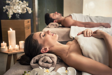 Man and woman lying down on massage beds at Asian wellness center