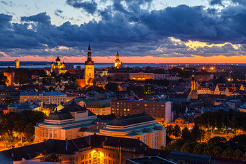 TALLINN, ESTONIA - JULY, 30, 2016: Orange sunset over old town. Cathedrals towers and modern buildings aerial view.