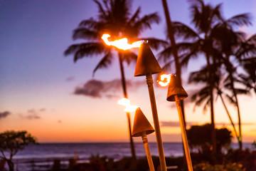 Hawaje zachód słońca z pochodniami ognia. Hawajska ikona, światła płonące o zmroku w nadmorskim kurorcie lub w restauracjach do oświetlenia i dekoracji na zewnątrz, przytulna atmosfera.