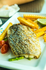 Grilled salted snapper with french fries on white plate