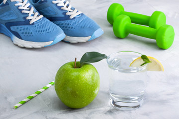 Sport composition with sports equipment glass water apple