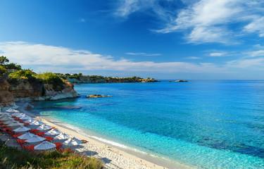 plaża z białym piaskiem i czystą błękitną wodą w pięknej zatoce z leżakami i parasolami, Kreta, Grecja