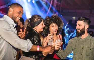 Wielorasowi młodzi przyjaciele tańczą w klubie nocnym - Szczęśliwi ludzie mają szaloną zabawę w klubie nocnym po imprezie - Koncepcja pijanego życia nocnego z imprezowymi chłopakami i dziewczynami świętującymi na festiwalu