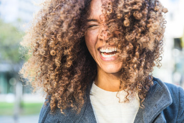 Curly woman laughing and shaking head