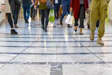 A modern floor with legs of a crowd in the background in Canary Wharf, London