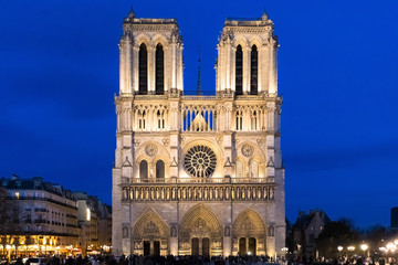 Notre-Dame de Paris Cathedral facade at dusk with illuminations