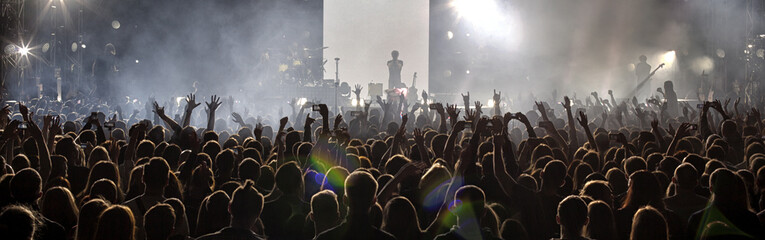 A crowd of people at a concert. Silhouettes of a crowd of fans in front of bright scene lights.