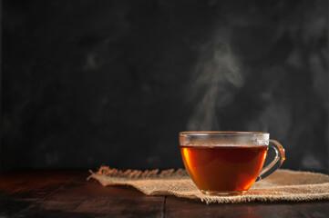 Filiżanka świeżo parzonej czarnej herbaty, ulatniająca się para, ciepłe miękkie światło, ciemniejsze tło.