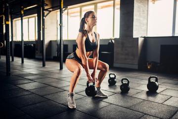 Kobieta robi ćwiczenia z ciężarem w klubie fitness