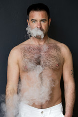 man with naked chest blowing out cigarette smoke