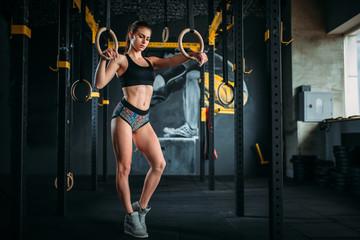 Szczupła kobieta sportowiec ćwiczenia na pierścienie gimnastyczne