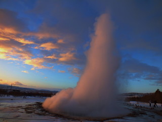 Shot of the ejection of the geyser Strokkur in Iceland during winter with a sunrise in the background.