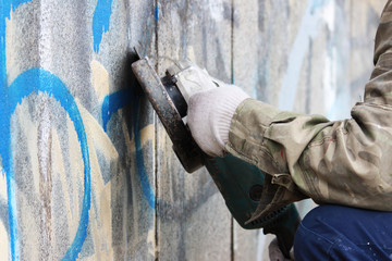 Removal of graffiti on a concrete wall of an underground passage with the help of a angle grinder.