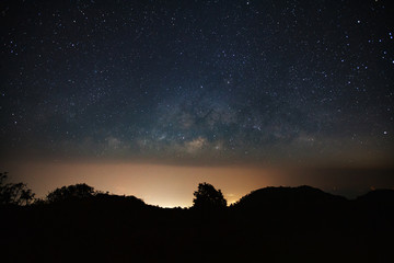 milkyway galaxy over moutain with city light and space dust in the universe