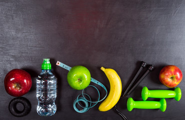 Dumbbell, jump rope, apple, banana and water bottle on black background. Top view fitness equipment background