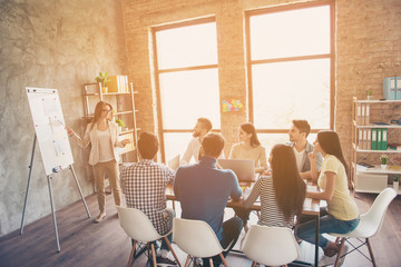 Young smart lady in glasses is reporting to the team of colleagues about the new project at the meeting with the white board. Workers are listening to her, all dressed in casual outfits