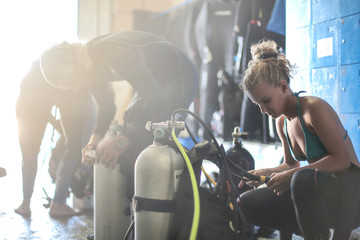 Three scuba divers dressing up for a dive session