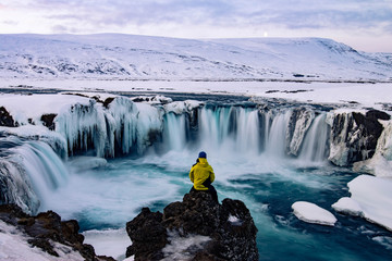 Odważny człowiek w Godafoss, Islandia zimą